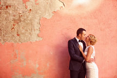 Bride and groom kissing against colorful wall Royalty Free Stock Photography