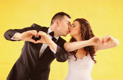 Bride and groom kissing against yellow wall Stock Photography