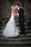 Bride and groom kissing on ancient stairs Stock Photo