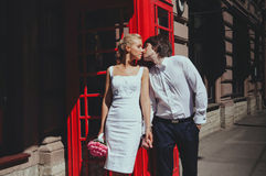 Bride and groom kissing on background of the phone booth. Tourism, travel people concept - happy senior couple over Stock Photos