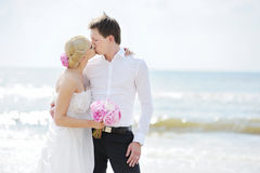Bride and groom kissing on a beach Royalty Free Stock Photos