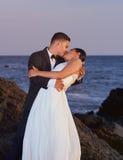 Bride and groom kissing on beach Stock Photos