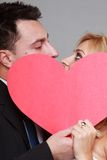 Bride and groom kissing behind red heart Royalty Free Stock Images