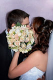 Bride and groom kissing behind wedding bouquet Stock Images