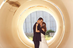 Bride and groom kissing in a big pipe Stock Photography