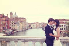 Bride and groom kissing on a bridge Royalty Free Stock Photo