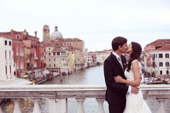 Bride and groom kissing on a bridge Stock Photography