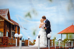 Bride and groom kissing on a bridge on their wedding day Royalty Free Stock Images