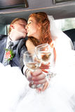 bride and groom kissing in car and clinking glasses Royalty Free Stock Photo