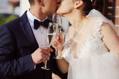 Bride and groom kissing and celebrating with glasses of champagne Royalty Free Stock Photo