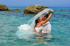 Bride & groom kissing in the clear blue sea water royalty free stock photo