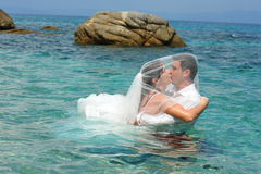 Bride & groom kissing in the clear blue sea water. Couple of newlyweds kissing in the clear blue sea water Stock Images