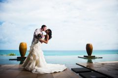 Bride and groom kissing on a clear Sunny day on a beautiful tropical beach. Romantic couple stock photo