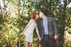 The bride and groom kissing each other in the forest Stock Photo