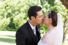 Bride and groom kissing each other in garden Stock Photo