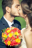 Bride and groom kissing each other outside Stock Photo