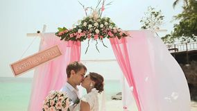 The bride and the groom are kissing each other. Wedding ceremony at the beach of the Philippines. stock video footage