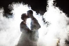 Bride and Groom kissing in fog at night Royalty Free Stock Photos