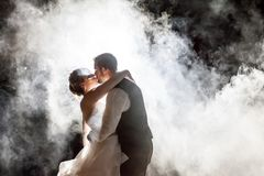 Bride and Groom kissing in fog at night royalty free stock images