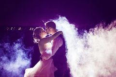 Bride and Groom kissing in fog with purple night sky. A backlit wedding couple kissing with smoke and fog around them at night with a dark violet sky Stock Image