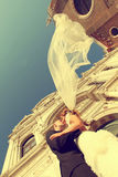 Bride and groom kissing in front of church. Sunny day stock photography