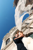 Bride and groom kissing in front of church. Sunny day stock photo