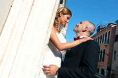 Bride and groom kissing in front of church. Sunny day stock photos