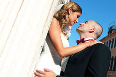 Bride and groom kissing in front of church. Sunny day stock images