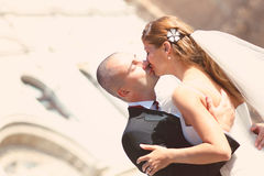 Bride and groom kissing in front of church. Sunny day royalty free stock images