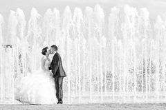 Bride and groom kissing in front of water fountain black and whi Royalty Free Stock Photos