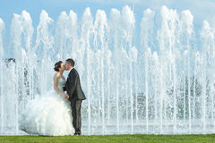 Bride and groom kissing in front of water fountain Stock Images