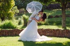 Bride and groom kissing in garden wedding stock image