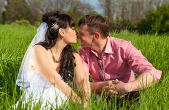 Bride and groom kissing in lips while sitting on meadow Royalty Free Stock Image