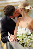 Bride and groom kissing in love. A portrait of a newly married couple kissing each other on their hotel balcony. They are holding hands, and the bride has a Royalty Free Stock Image