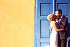 Bride and groom kissing near blue door Stock Image