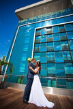 Bride and groom is kissing near the building Royalty Free Stock Photos