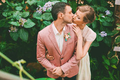 Bride and groom kissing near bush with flowers Royalty Free Stock Photo