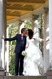 Bride and groom kissing near columns Stock Images