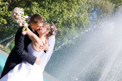 A bride and a groom kissing near the fountain Stock Photo