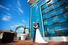 Bride and groom is kissing near the glass building Stock Photos