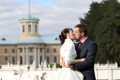 Bride and groom kissing near palace Royalty Free Stock Photos