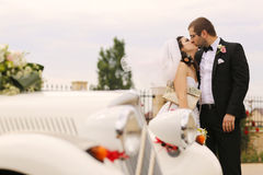 Bride and groom kissing near retro car Royalty Free Stock Images