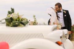 Bride and groom kissing near retro car Stock Photography