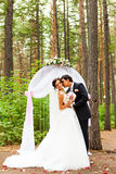 Bride and groom kissing near the wedding arch Royalty Free Stock Image
