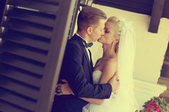 Bride and groom kissing near window Royalty Free Stock Photography