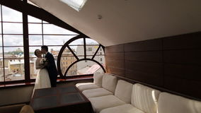Bride and groom kissing near the window and smilling stock video
