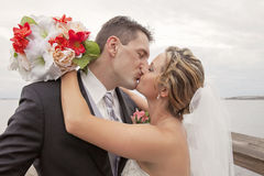 Bride and Groom kissing. A bride and groom kissing outdoors Royalty Free Stock Photo