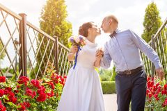 Bride and groom kissing outdoors. Wedding day of happy bridal couple, newlywed woman and man embracing with love in the Stock Photo