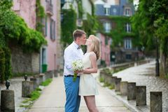 Bride and groom kissing on a Parisian street Stock Images
