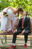 Bride and groom. Kissing in the park on a bench Royalty Free Stock Images